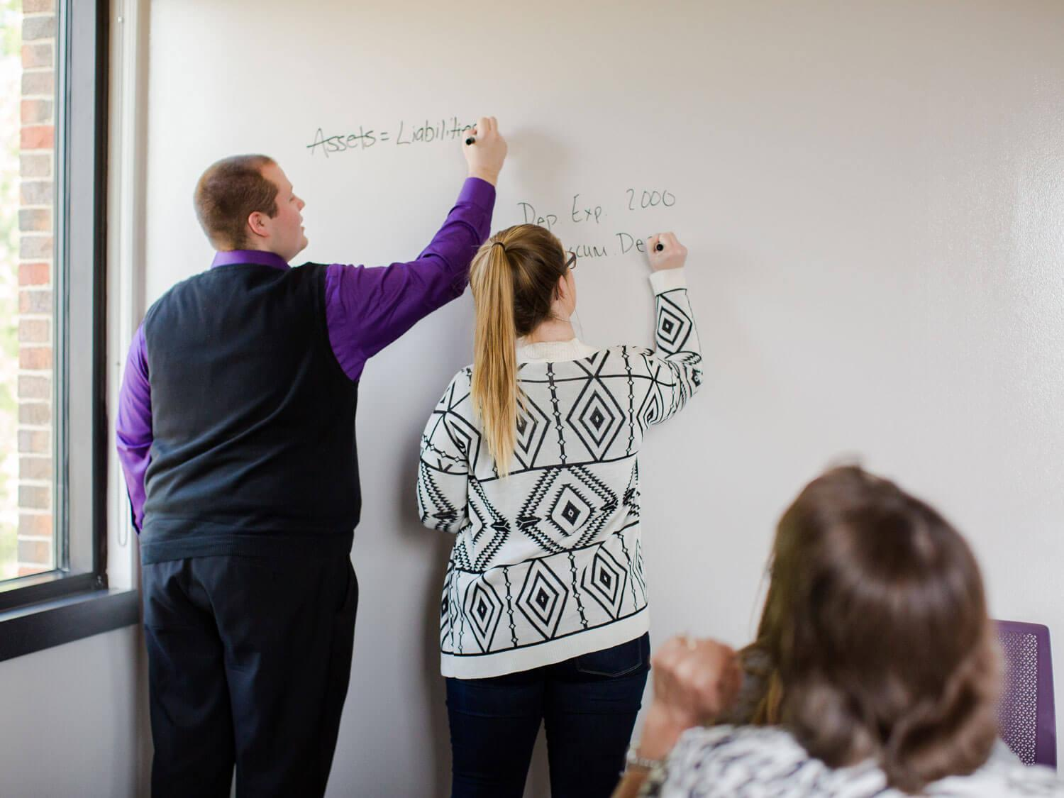Students work out accounting problems on whiteboard
