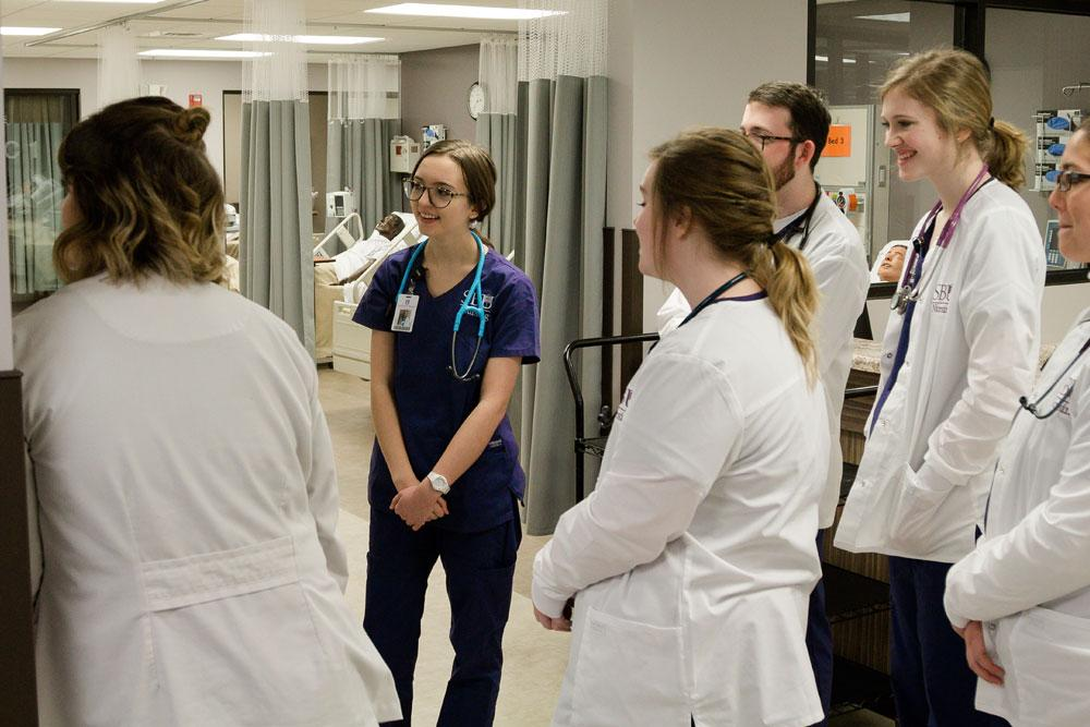 Group of nursing students stand in simulation lab