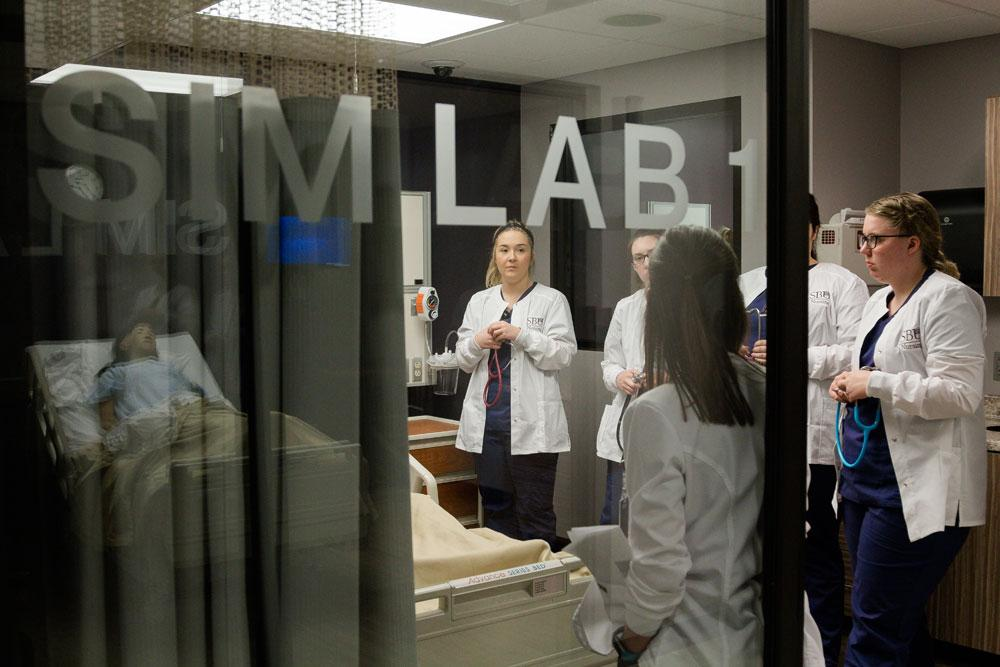 Group of nursing students listen to instructor inside a simulation lab