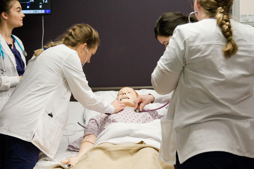 Group of nursing students use stethoscopes to listen to mannequin's heart beat