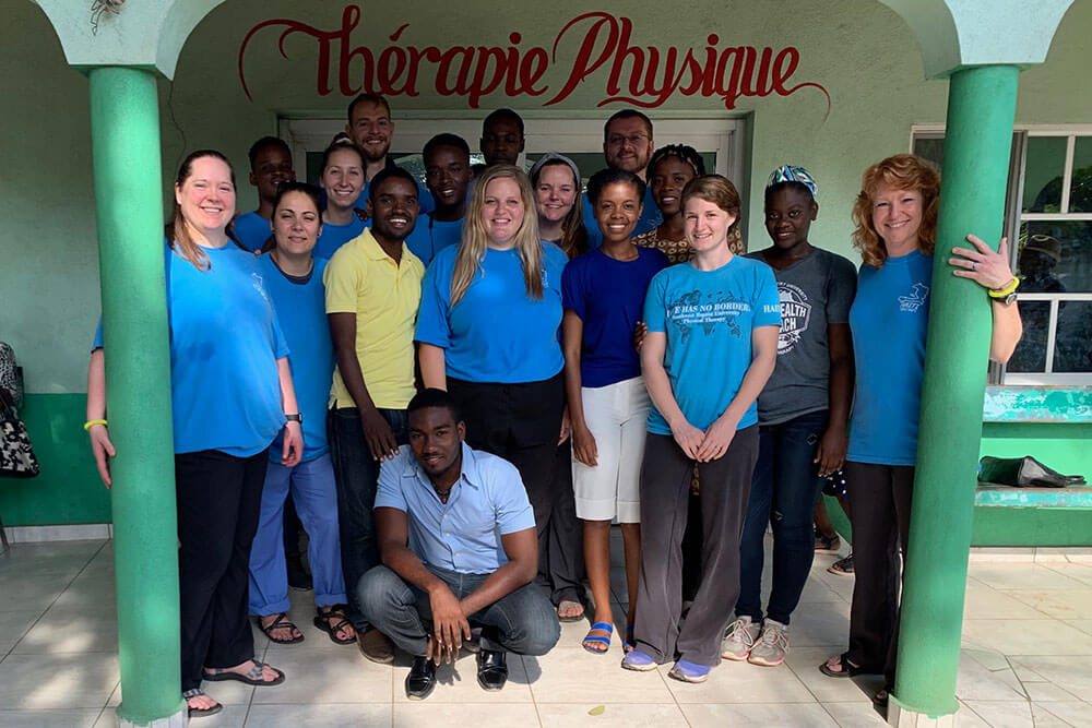 SBU Physical Therapy students and professors pose for group photo with local Haitians outside clinic