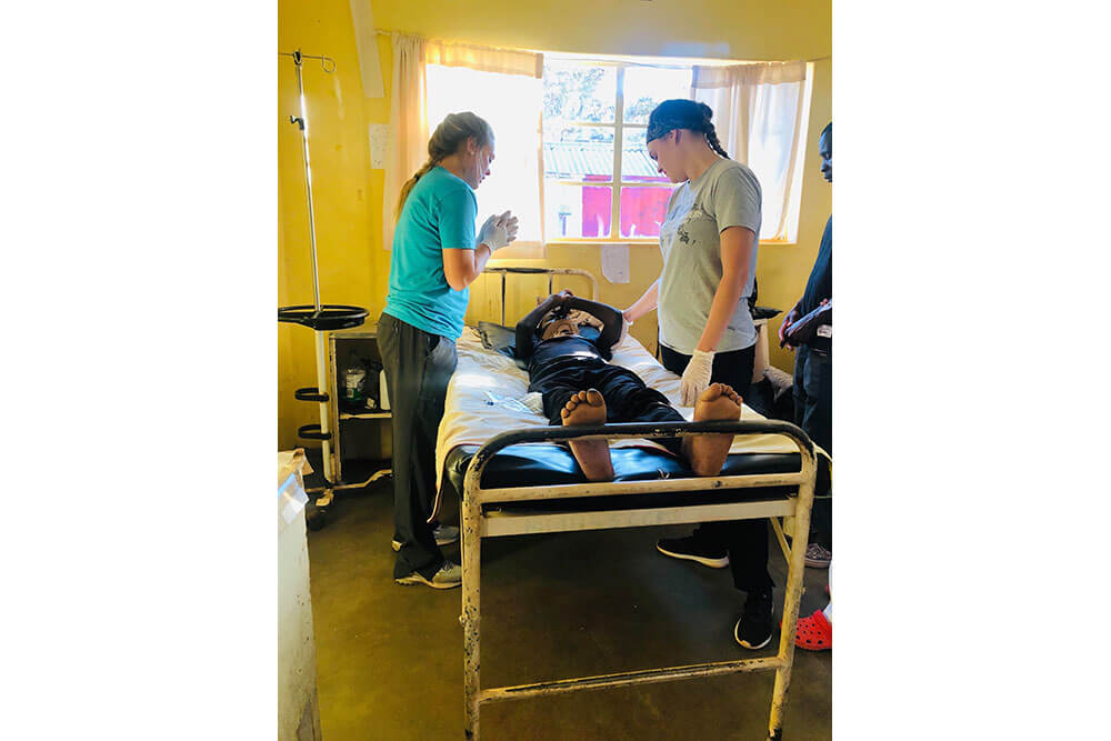 Two female physical therapy students stand over patient lying in bed