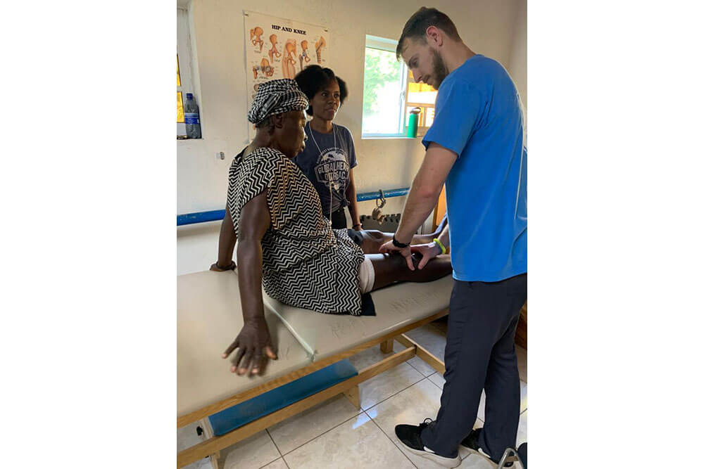 SBU Physical Therapy student examines patient's leg in Haiti