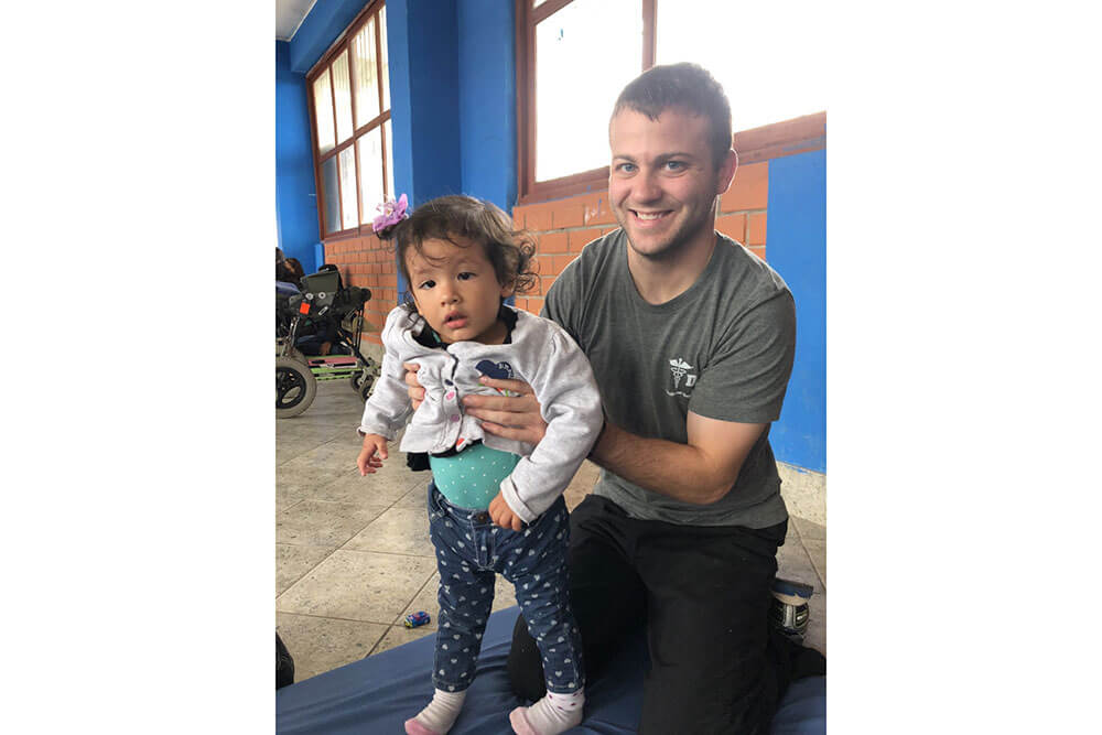 SBU Physical Therapy student smiles while holding small female toddler