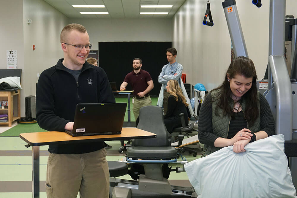 male instructor stands at laptop while female student carries supplies