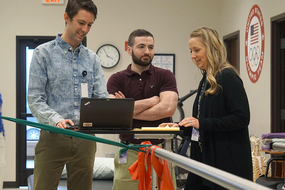 two male students stand behind laptop screen as female instructor provides feedback