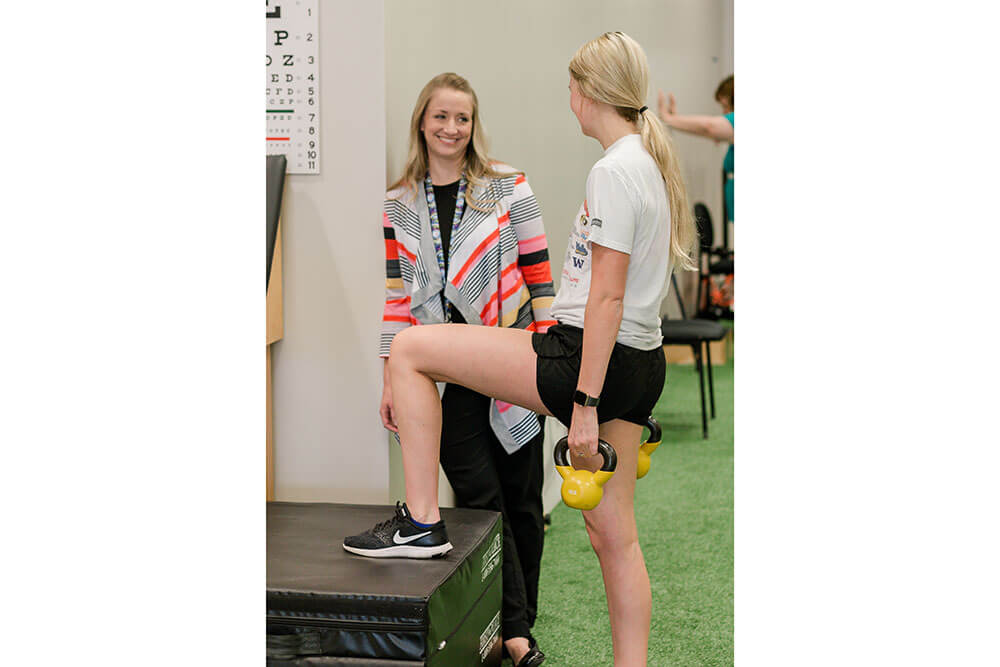 female instructor gives instructions to female patient doing exercises