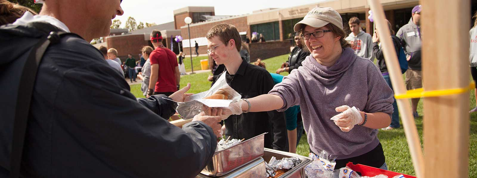 food services worker hands hot dog to man during Homecoming carnival