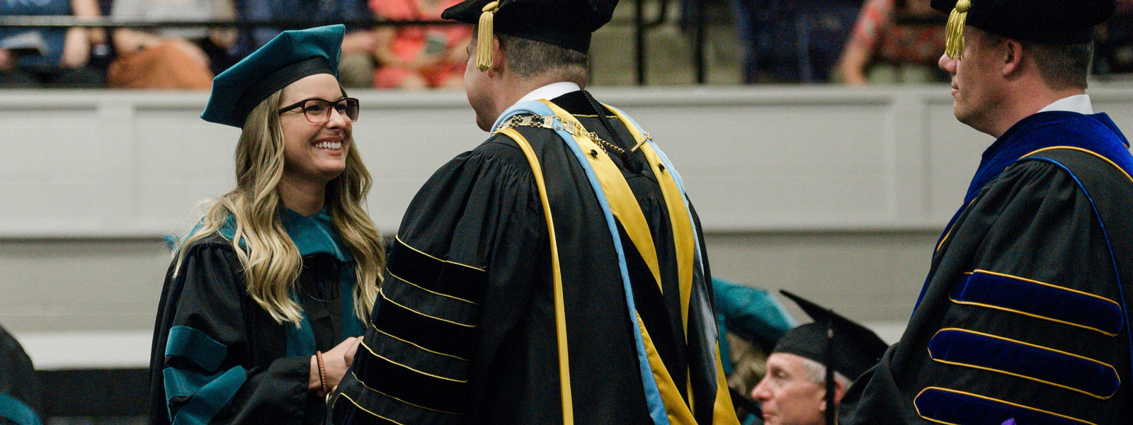 physical therapy student receives diploma at commencement ceremony