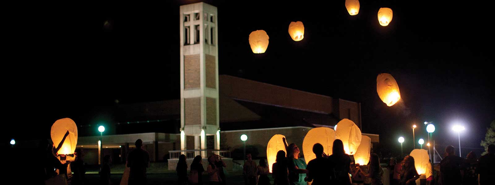 students release lanterns into night sky in front of bell tower