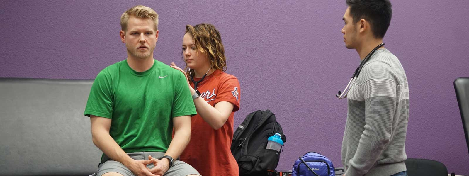student observes instructor demonstrating physical therapy exercise with patient laying on table