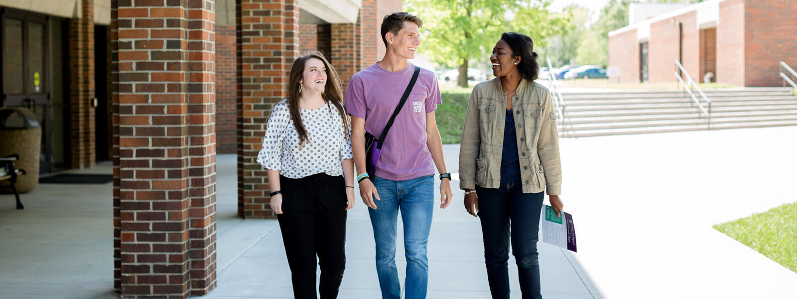 three students walking on sidewalk on campus