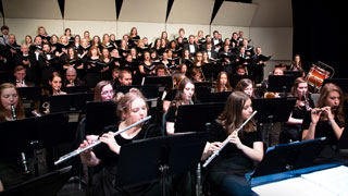 Instrumental and choral ensembles perform on stage together