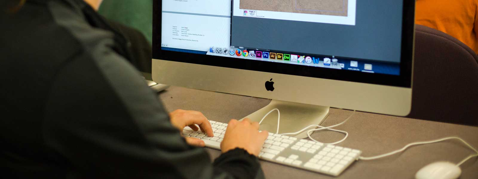 students working on graphic design projects on large Mac computers