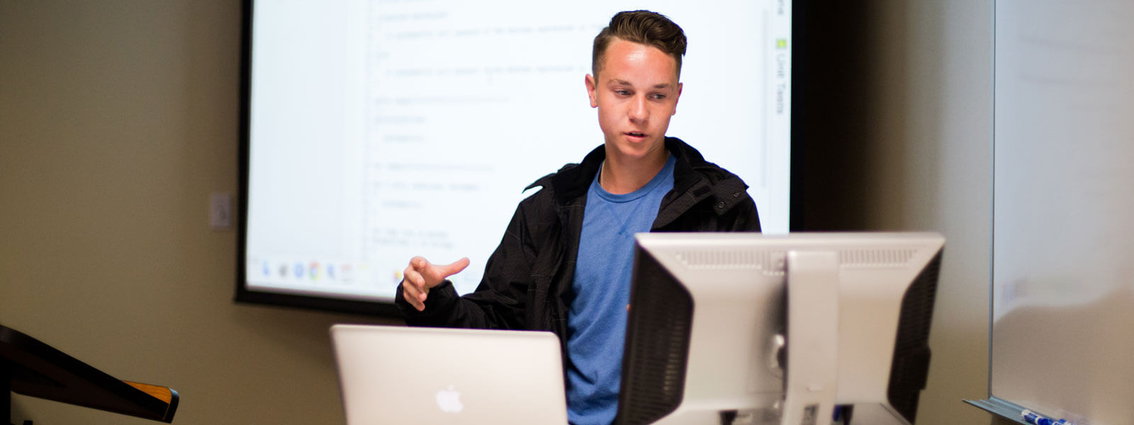 student looks at computer screen while giving class presentation