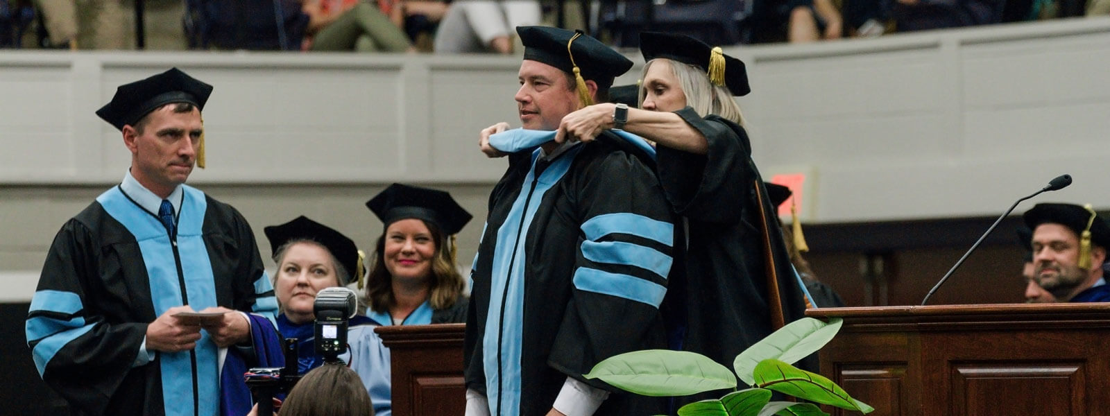 doctor of education graduate shakes president's hand as he receives diploma on graduation stage