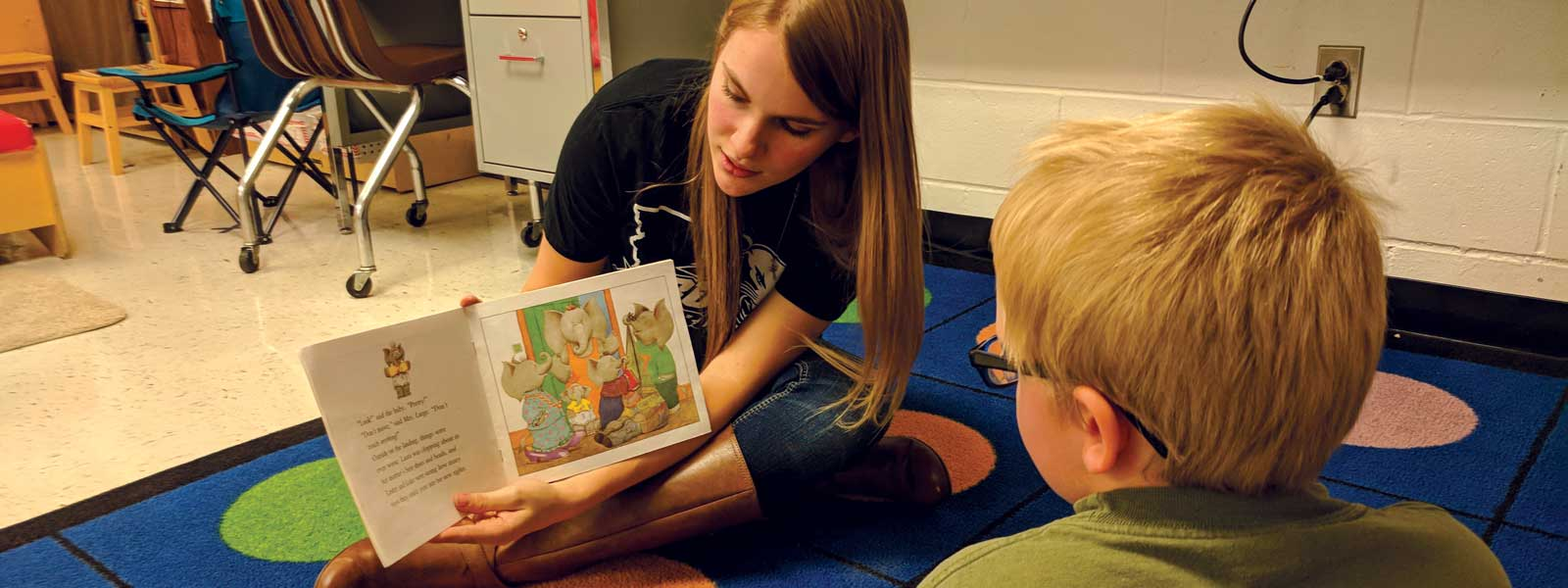 female college student reads book to young boy