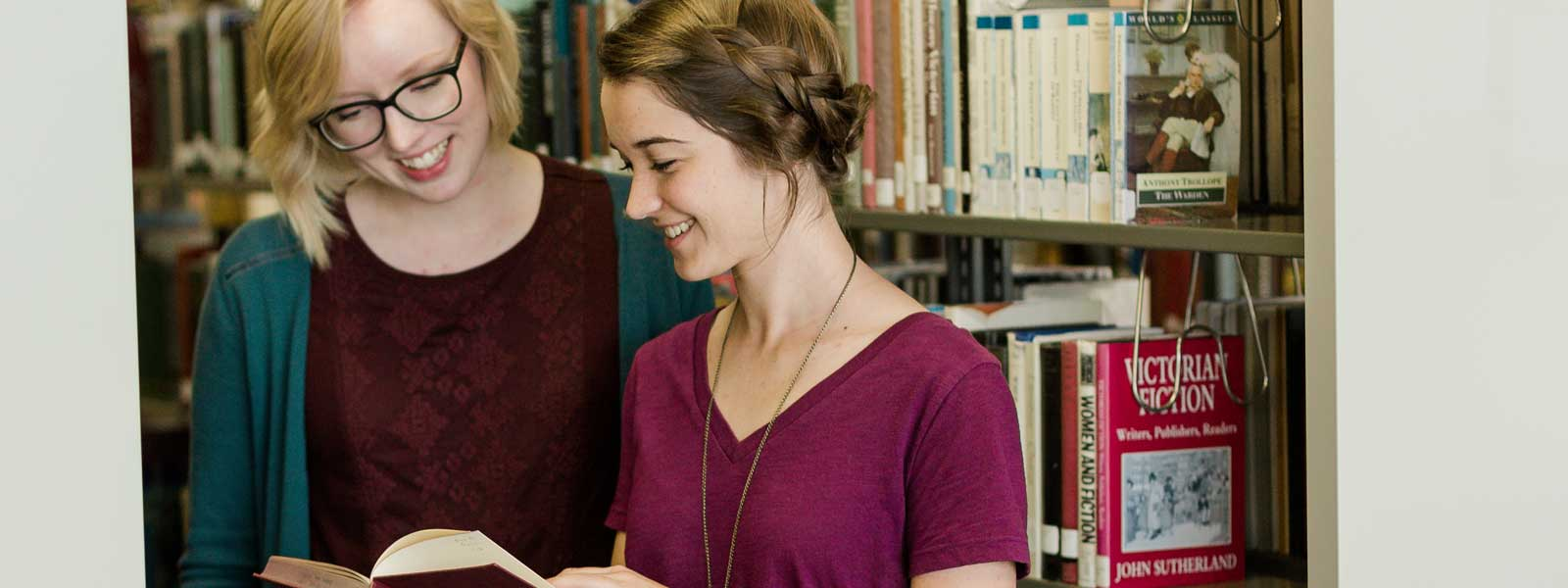 two students look at book in library