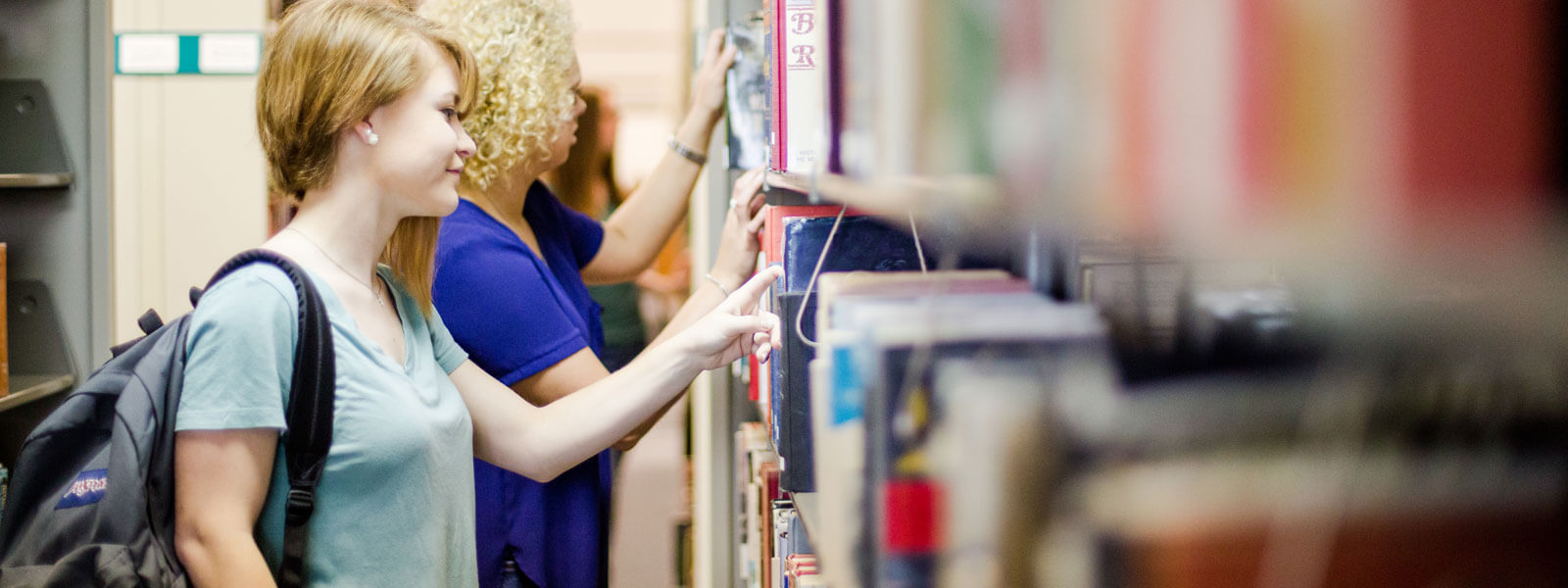 students browse shelves in library