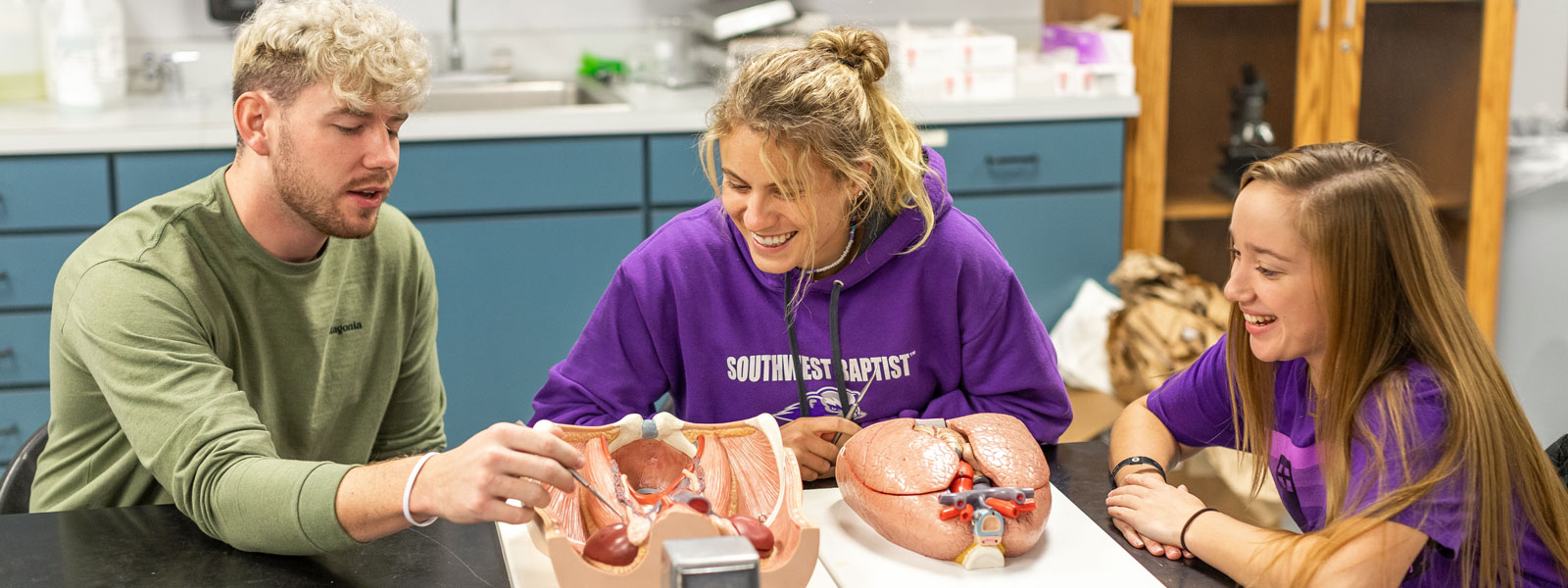 biology professor and students examine molecule example in lab