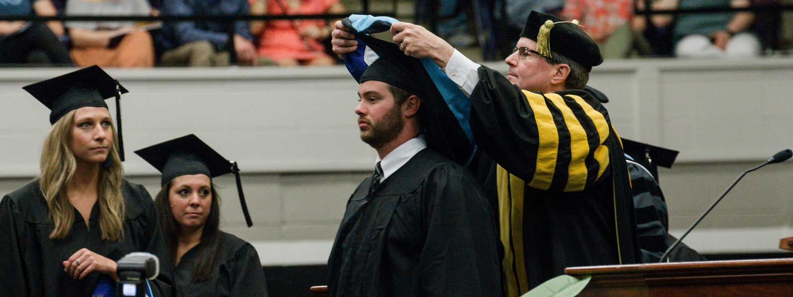 college dean put hoods around neck of graduate while other graduates watch and wait their turns