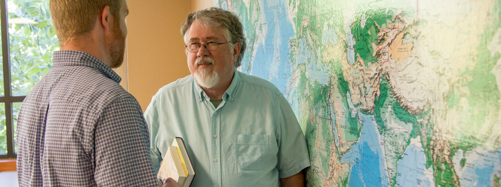 ministry professor holds books and talks to student while standing in front of world map on wall