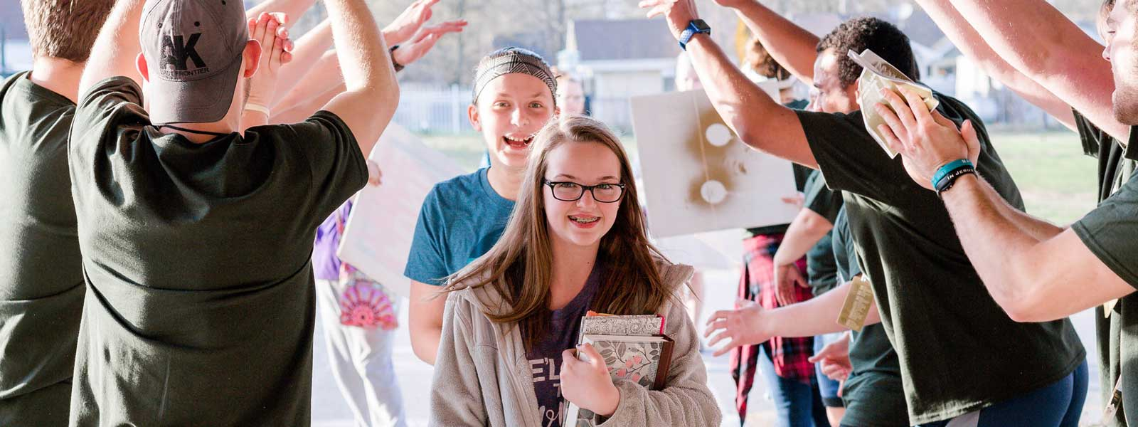 two young girls smile as they are welcomed into church camp by enthusiastic youth leaders