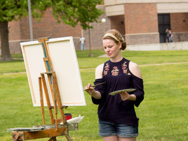 Female art student working on painting outside
