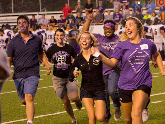 SBU students running on football field