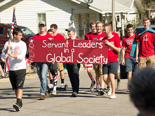Students in parade with banner that says 'Servant leaders in a global society'